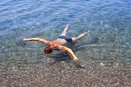 briefs: A boy swimming floating as to play dead