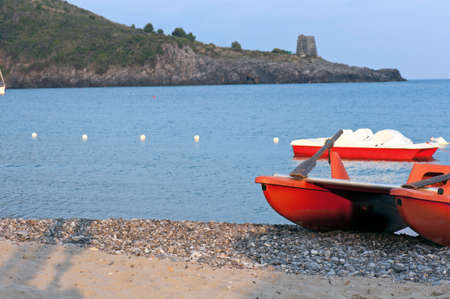 Pedal paddle and lifeboat on the shoreline. photo