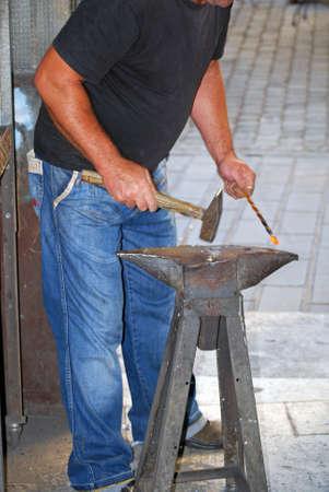 A blacksmith forging an iron piece on the anvil photo