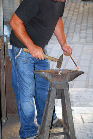 A blacksmith forging an iron piece on the anvil photo