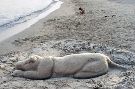 Dog figure moulded on the sand with a child playing at beach Stock Photo