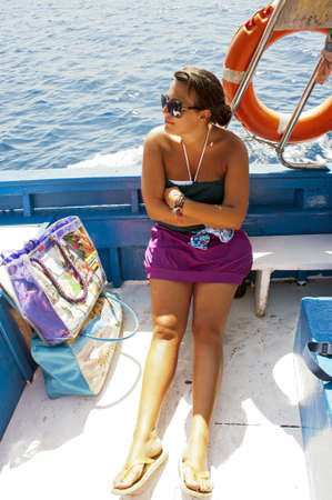 A pretty girl sat on a boat during trip photo