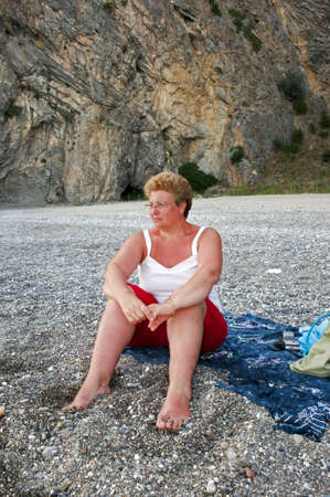 A lady relaxing at beach sat on the foreshore Stock Photo - 10339464