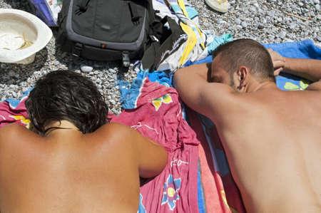 Mladý muž a žena, opalování, zatímco ležel nahý na pláži Reklamní fotografie - 10339463
