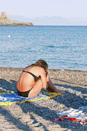 broken back: A girl sunbathing alone on the sand at the beach Editorial