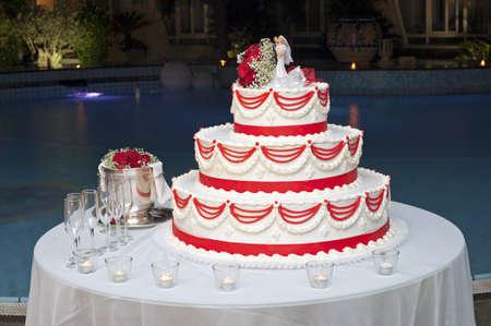 Bruidstaart klaar voor het snijden ceremonie in het zwembad 's nachts Stockfoto