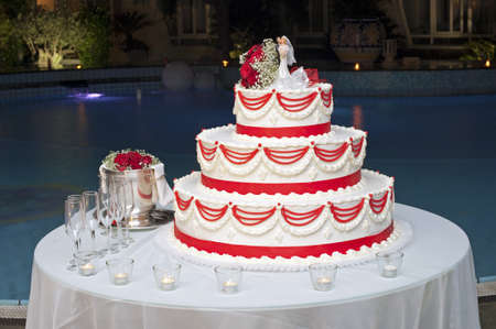Wedding cake ready for the cutting ceremony in the swimming pool at night photo