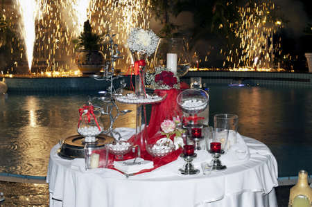 Wedding table with fireworks in the swimming pool at night