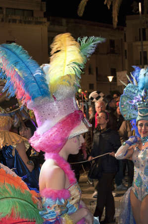 fluffy tuft: People dressed up for carnival in the street at night, Sciacca, Italy
