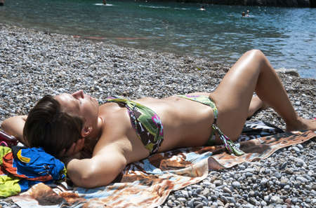 Young woman tanning at beach photo