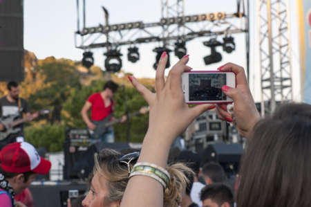 Teenagers watching an outdoor rock concert