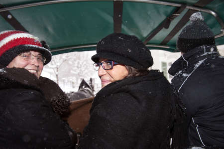 Two women on a sleigh during a snowfall photo