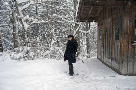 A girl near a hut during a snowfall  photo