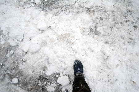 Detail of a person s leg walking in a road covered with snow photo