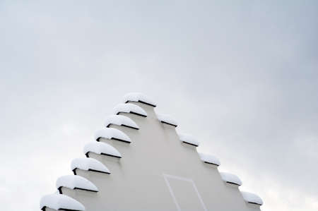 Geometrical roof's shape snow-covered against the sky Stock Photo - 17395892