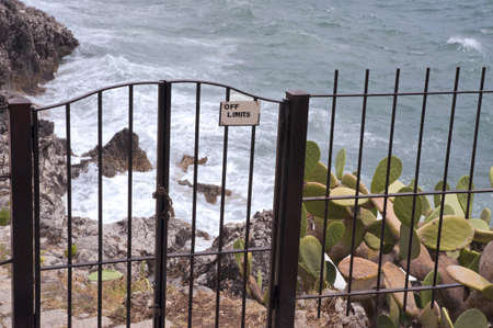 steep cliffs sign: A close gate above a rocky coastline