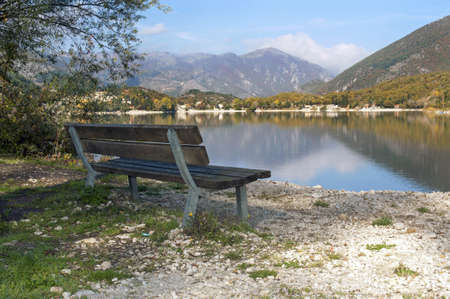 A wooden bench along the riverside, Lake Scanno, Abruzzo, Italy photo