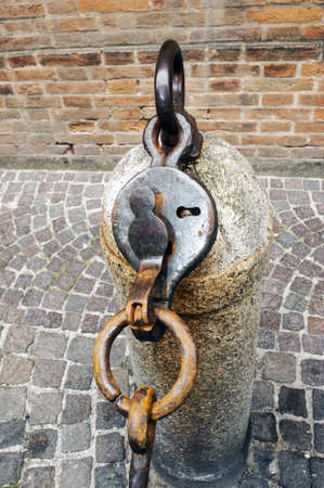 deadbolt: Ancient urban pillar with deadbolt to delimit the passage by chains