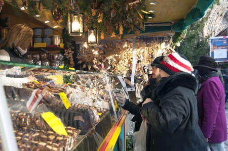 Mensen genieten van kerstmarkt (Christkindlmarket) met kraampjes in Duitsland.