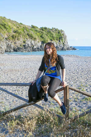 paling: A young woman sat on a paling at beach