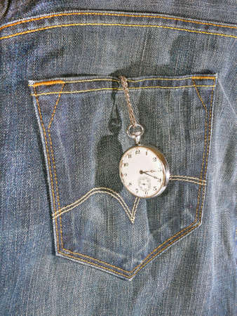 Blue-jeans with a watch hanging out of the pocket