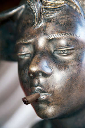 smoking a cigar: Bronze of a boy smoking a cigar