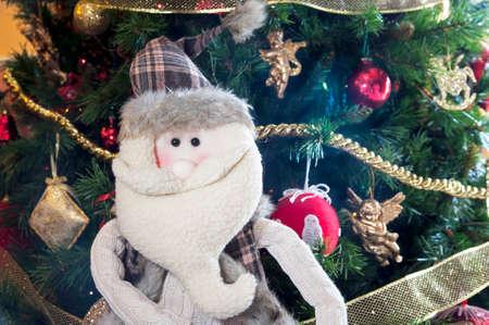gewgaw: Snowman doll near a Christmas tree