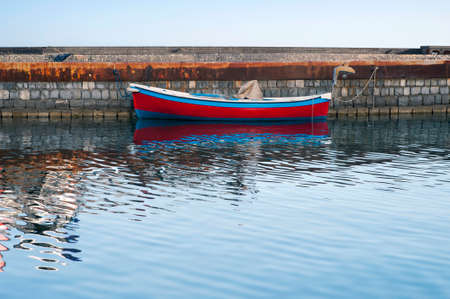 dockside: A rowboat moored along the dockside Stock Photo