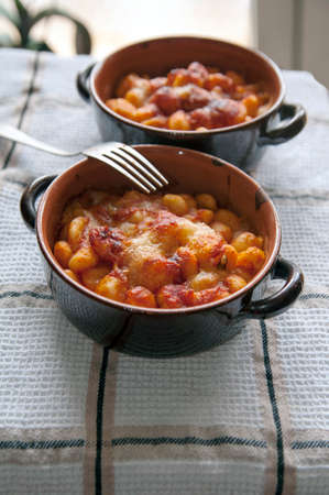 dinnertime: Pots with baked gnocchi with sauce Stock Photo