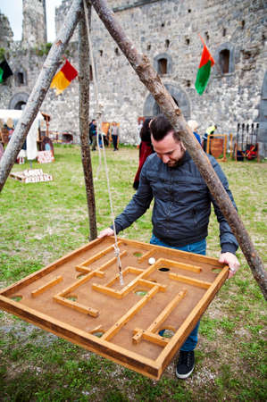 Young man playing with a medieval wooden game photo