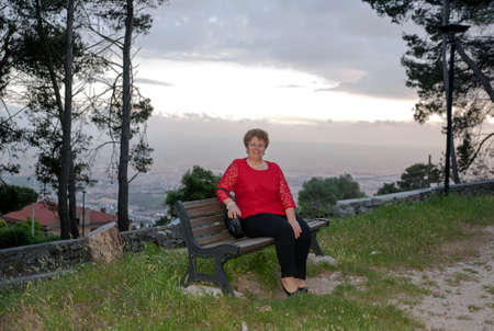 Woman sat on a bench in the evening