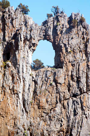Amazing large hole like an arched window in the cliff along the coast of Palinuro, Italy, Europe.