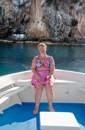 Woman sat on a motorboat's poop during a boat trip alongshore, Palinuro, Italy.