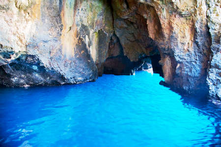 Inside the striking Blue Grotto where some sunbeams makes the cobalt blue seawater becomes light blue