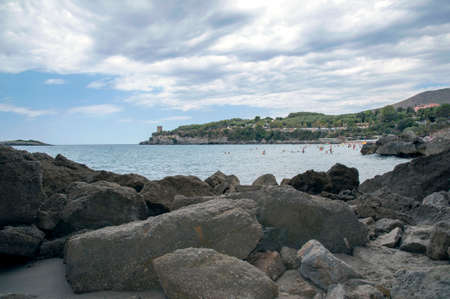 People enjoying in a bay with big stones on the sandy beach Stock fotó