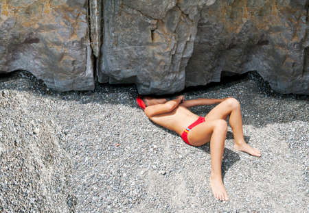 Boy lying down under a rock's fissure on the beach