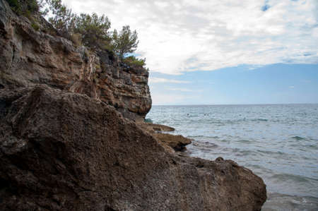 People swimming along the rocky and jagged coast, Marina di Camerota, Italy Stockfoto