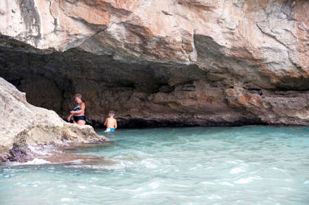 A woman with a boy swimming in a big cave at seashore