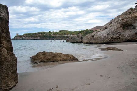 People having fun in a wondrous cove with a stony beach, Marina di Camerota, Italy