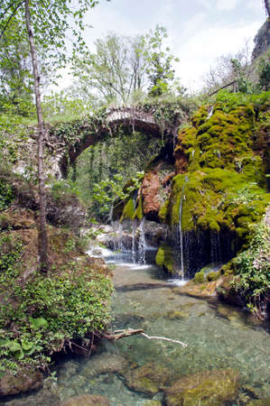 An old stone bridge over some small waterfalls and mossy rocks, Casaletto Spartano, Salerno Italy.