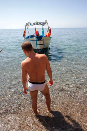 A cool guy about to climb on a motorboat moored in the cove. Beach, sailing.