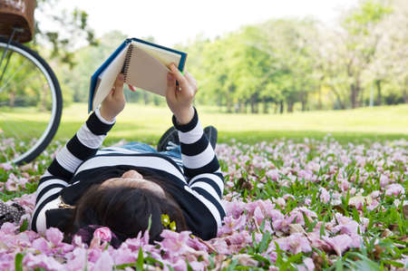 Asian woman reading booklet on the grass photo