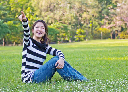 Asian woman pointing the tree photo
