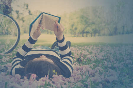 Asian woman reading booklet on the grass  Vintage style  photo