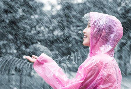 Asian woman in pink raincoat enjoying the rain in the garden