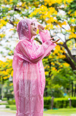 Asian woman in pink raincoat checking for rain in the garden  Stock Photo