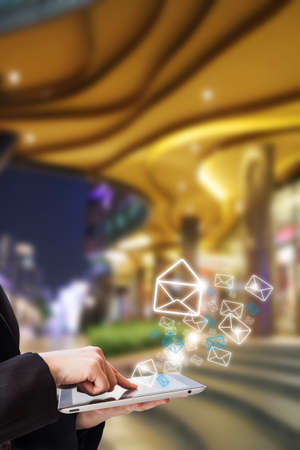 Businesswoman sending email in front of the shopping mall photo