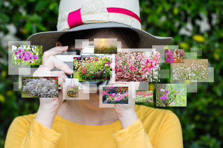 snapping fingers: Woman taking photos in the garden Stock Photo
