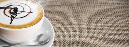 Coffee cup and saucer on sackcloth background photo