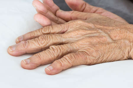 wizened: Old hands on the bed
